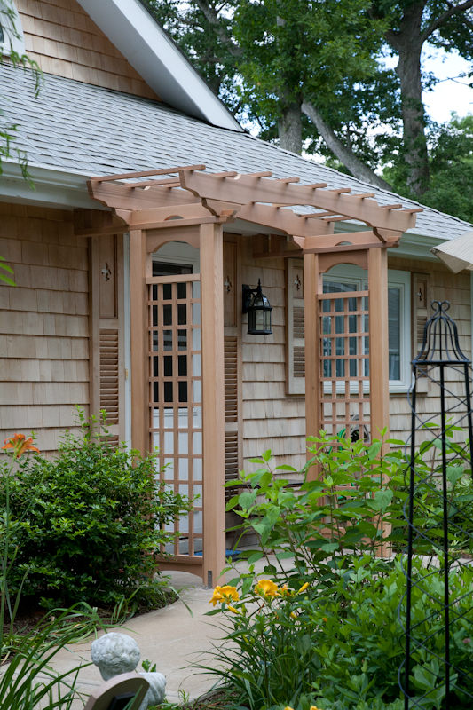 A cedar arbor with plexiglass to provide cover from the weather.