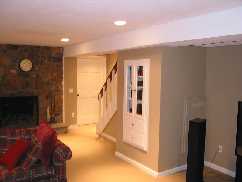 Finished basement with a fireplace and a built-in cabinet for audio equipment under the stairs in Farmington CT
