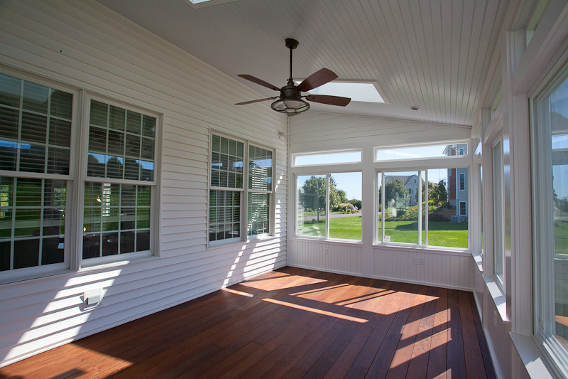Interior of an enclosed porch built on a deck with sliding windows.